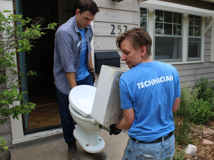 Resource Central employees Max Hartmann (left) and Neka Sunlin haul the MacFarland family's vintage toilet out of their Longmont, Colorado home.