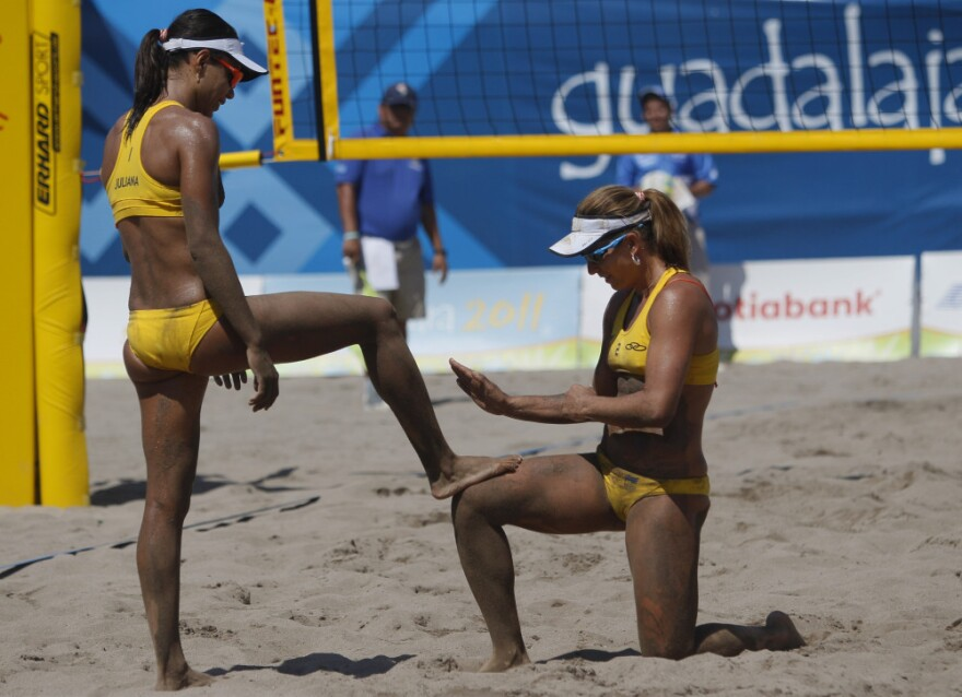Brazil's Larissa Franca (right) cleans the feet of teammate Juliana Silva as they celebrate a point during a women's beach volleyball match against Cuba at the Pan American Games in Puerto Vallarta, Mexico, in October 2011.