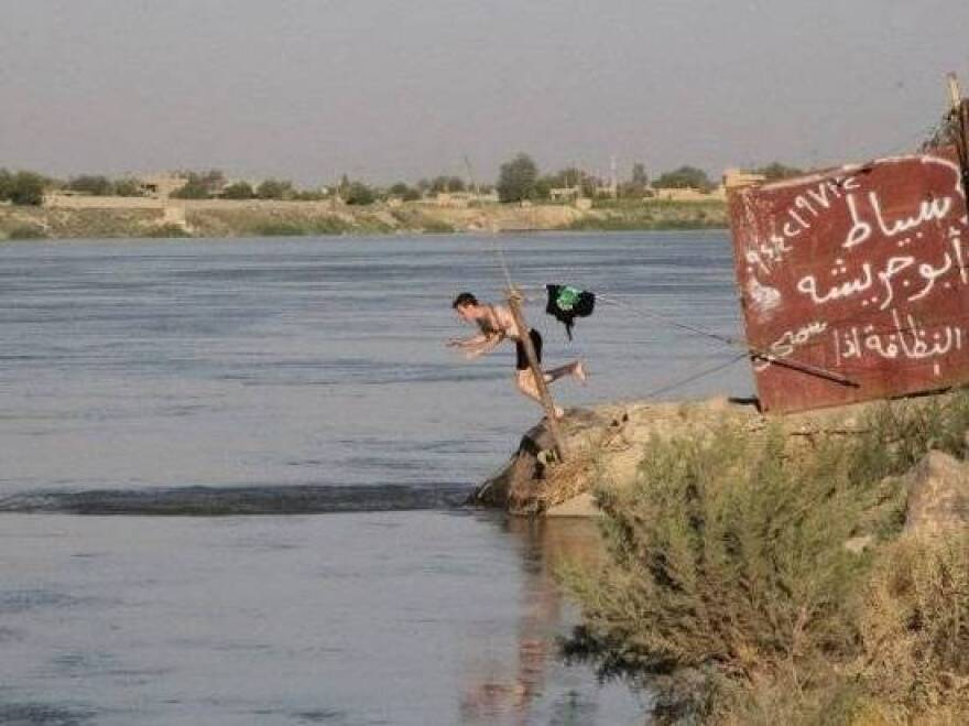 Kassig dives into the Euphrates River during a humanitarian mission to the eastern Syrian city of Deir Ezzor.