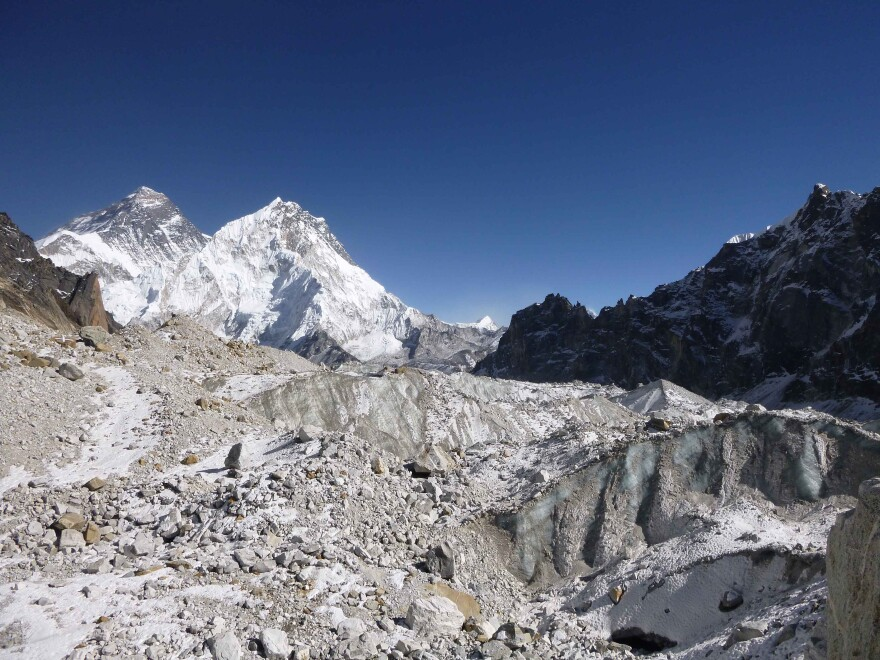 A view of Changri Nup, a typical debris-covered glacier in the Everest region, highlights the glacier's complex surface characteristics, including patches of rock debris and exposed ice cliffs.