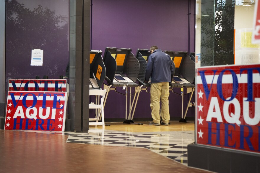 A man stands at a voting machine