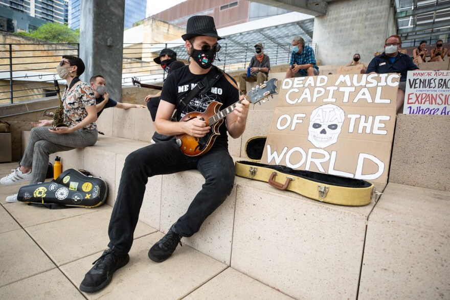 """Andrew Noble plays guitar next to a sign that reads, """"Dead Music Capital Of The World,"""" during a demonstration at City Hall."""
