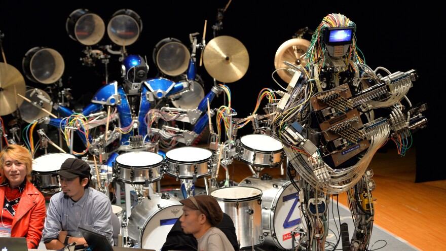 """Robot guitarist """"Mach"""" and a robot drummer """"Ashura"""", members of a robot rock band """"Z-Machines"""", perform music at the National Museum of Emerging Science and Innovation."""
