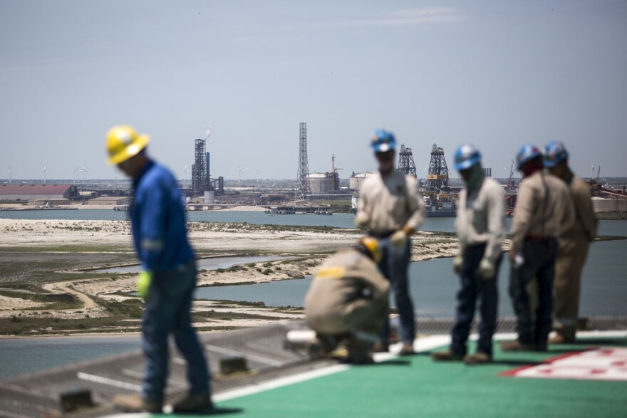 Laborerers work on the helipad of an offshore oil platform in the Gulf of Mexico.
