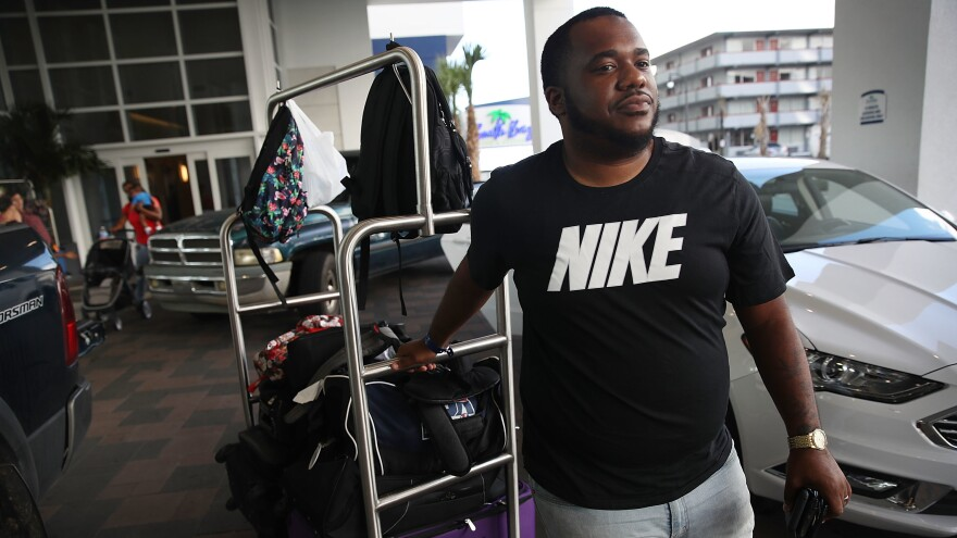 Marcus Thurston and his family leave their hotel in Myrtle Beach, S.C., on Tuesday, cutting their vacation short ahead of Hurricane Florence's arrival.