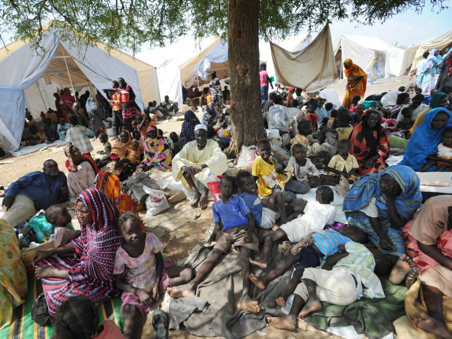 A handout picture released by the United Nations Mission in Sudan (UNMIS) on June 10 shows residents of Kadugli seeking shelter outside UNMIS sector headquarters after fleeing fighting in Kadugli town.
