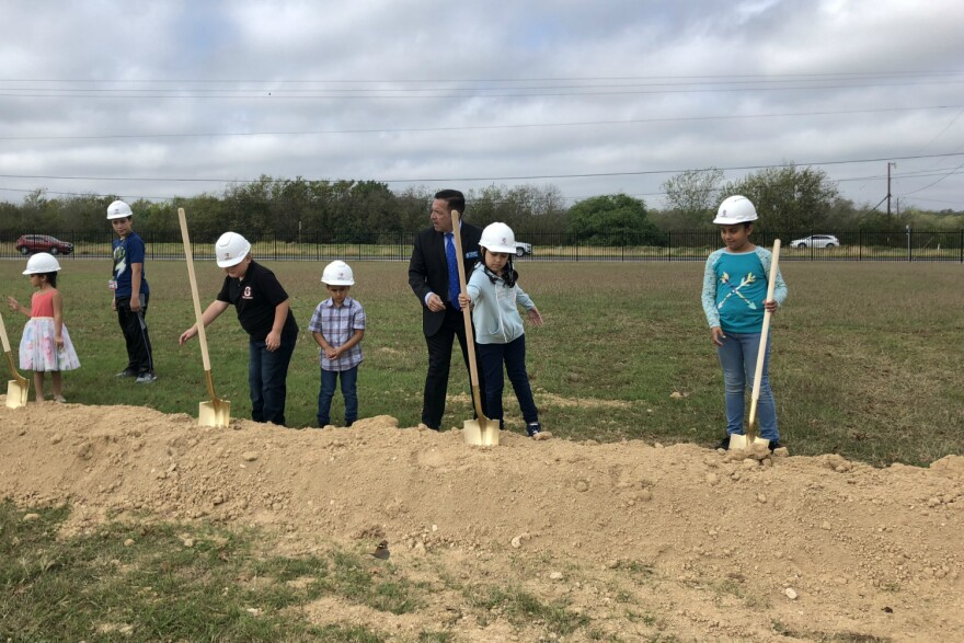 Southside ISD spokesman Randy Escamilla helps students grab shovels for the ceremonial groundbreaking of a medical clinic next to the district's central office Nov. 5, 2018.