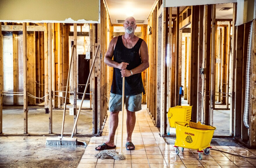 "Phillip ""Mooney"" Brignac, 58, works on cleaning up his home, where he's lived since 1991, raising two children during that time. ""We will definitely rebuild. We are St. Amant strong. We will do whatever we've got to do,"" he said."