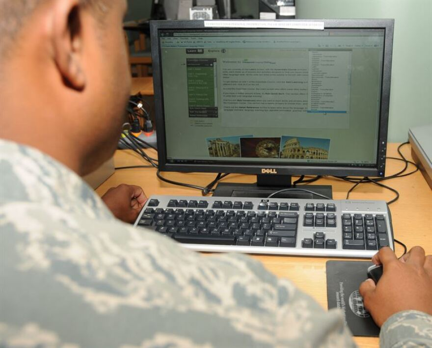Man in military uniform using a computer