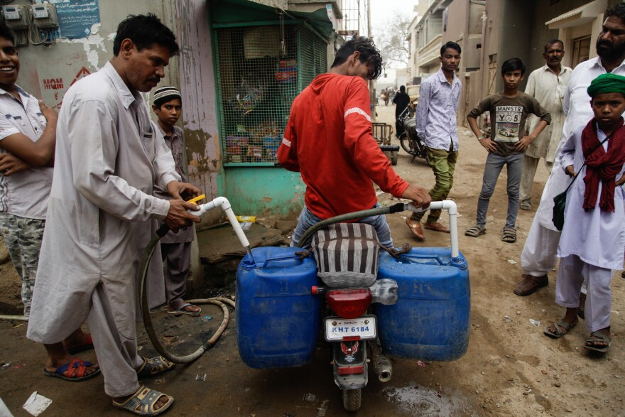 A young man fills the jerrycans tied to his motorbike with water in the Korangi slum.