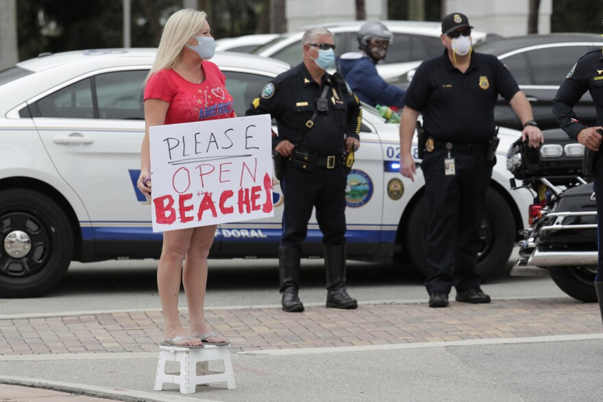 "A protestor, who did not want to be identified, holds a sign reading ""Please Open Beaches"" as Florida Gov. Ron DeSantis speaks at a news conference during the new coronavirus pandemic, Thursday, May 14, 2020, in Doral, Fla. DeSantis has signed an executive order for the gradual reopening of Miami-Dade and Broward counties on May 18. (AP Photo/Lynne Sladky)"