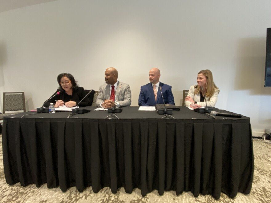 Four panelists sit at a table at the forum.