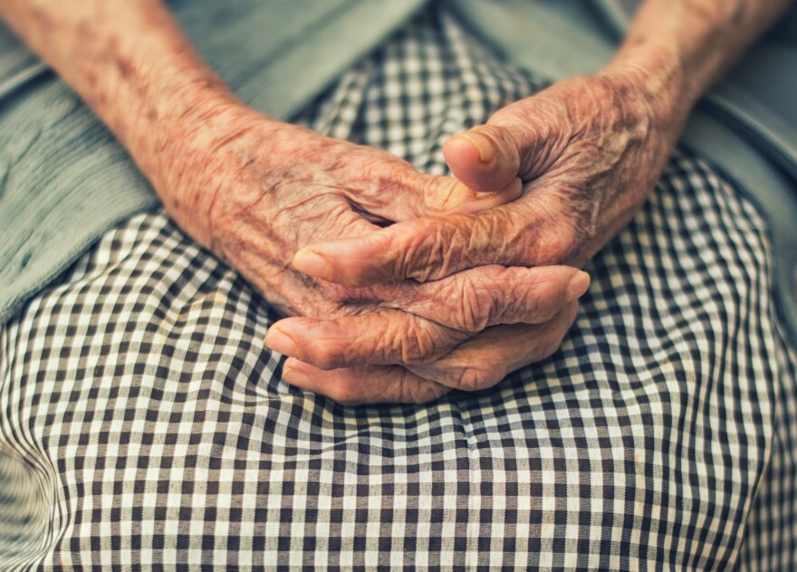 A set of wrinkled hands sits folded in a woman's lap