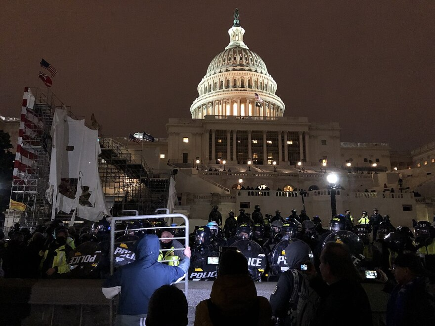 1280px-Riot_police_and_protester_outside_United_States_Capitol_at_evening_20210106.jpg