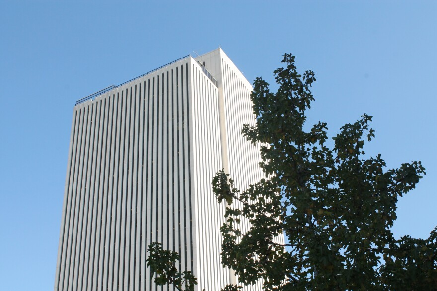 Picture of a tall white building against blue sky.