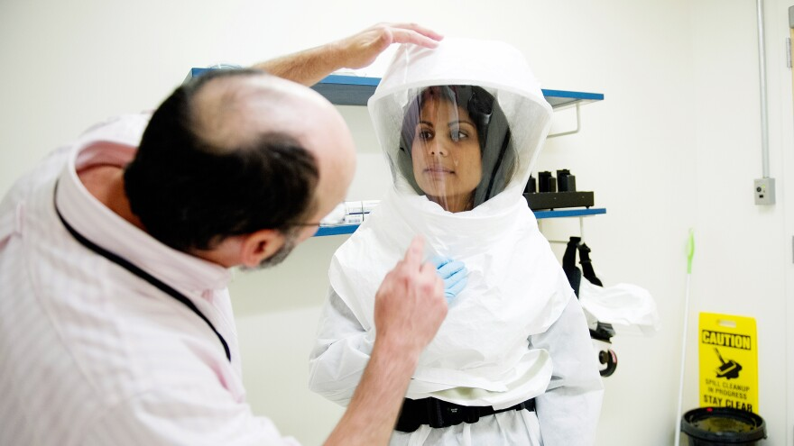 Nahid Bhadelia gets a lesson in donning a protective suit before her trip to Sierra Leone.