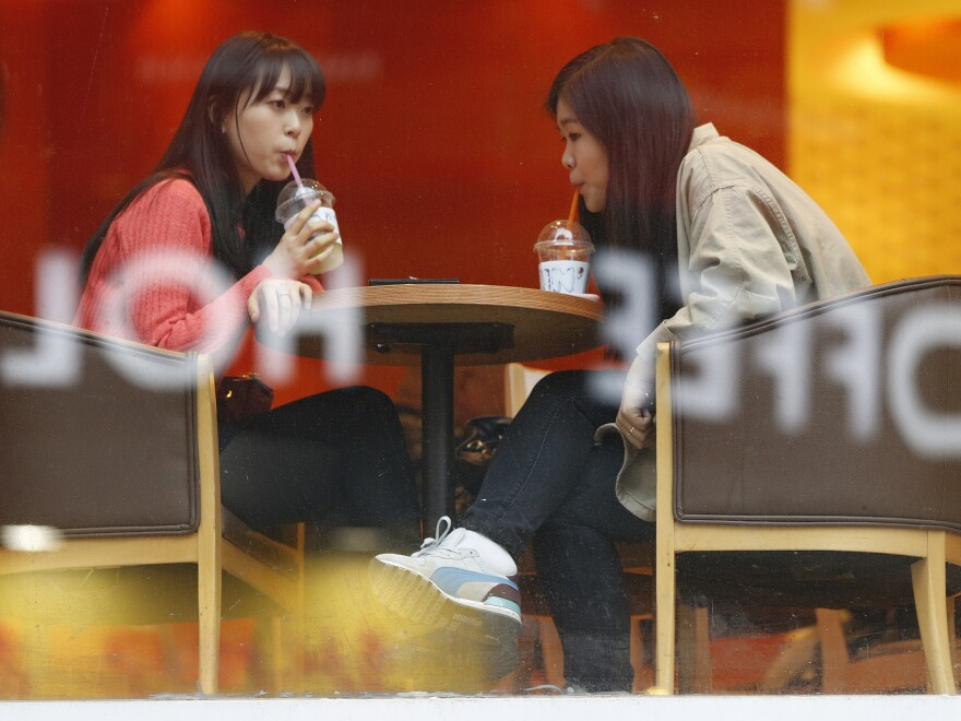 Two women sit at a cafe Monday in central Seoul, South Korea. While North Korea has been issuing threats on a daily basis, many South Koreans say they're more bored than worried.