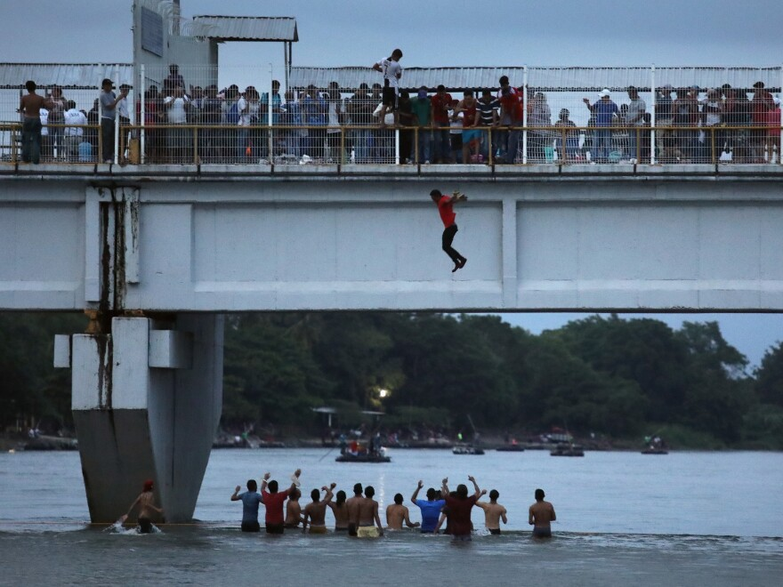 An migrant jumps off a bridge to enter Ciudad Hidalgo, Mexico, from Guatemala on Saturday.