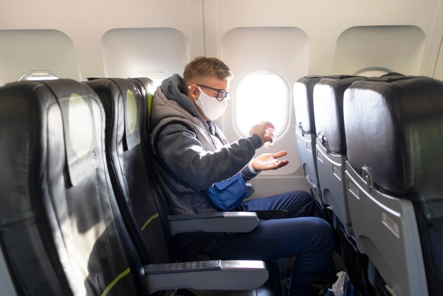Guy in airplane with a medical protective sterile mask on his face, sitting on plane while applying sanitizer to disinfect his hands against coronavirus.