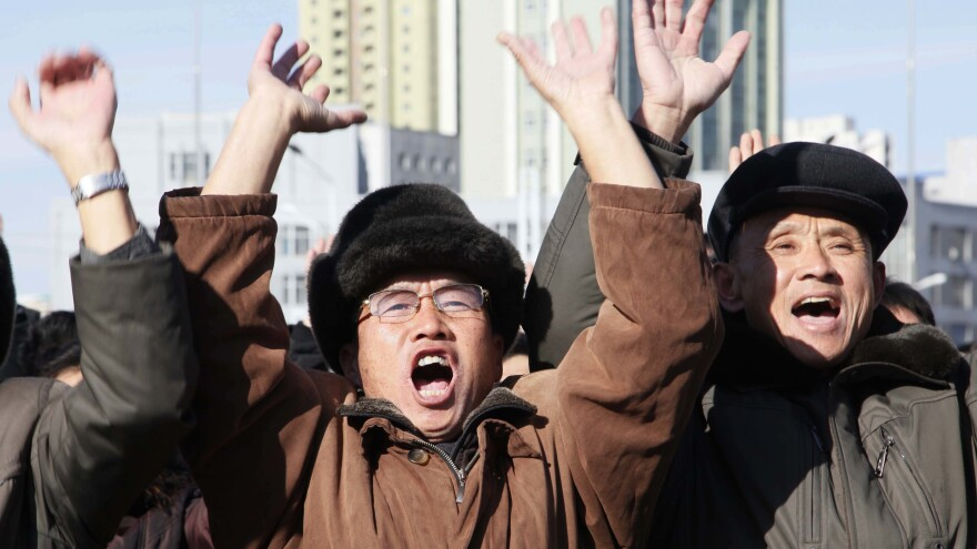 People at the Pyongyang Train Station in North Korea cheer as they watch the news broadcast announcing leader Kim Jong Un's order to test-fire the newly developed inter-continental ballistic missile Hwasong-15.