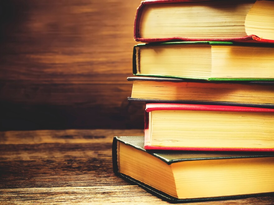 Stack of books on the dark wood background.