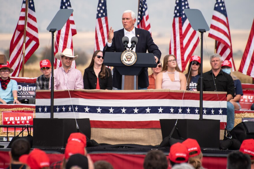 Vice President Mike Pence stands at a podium on a raised platform with a stars and strips banner.