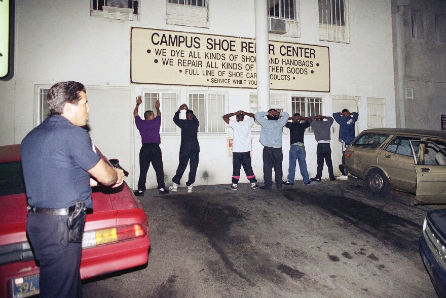 A Los Angeles police officer points his gun on seven men near the University of California, Los Angeles on April 30, 1992. The men were detained and later released. Store windows were broken and merchandise was stolen in the upscale college community.