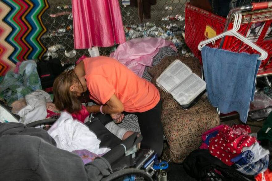 "A woman sleeps with her wheelchair nearby at what one Miami-Dade County School Board member called ""an opioid and sex den"" located in an expressway underpass near several schools in Overtown in October 2018."