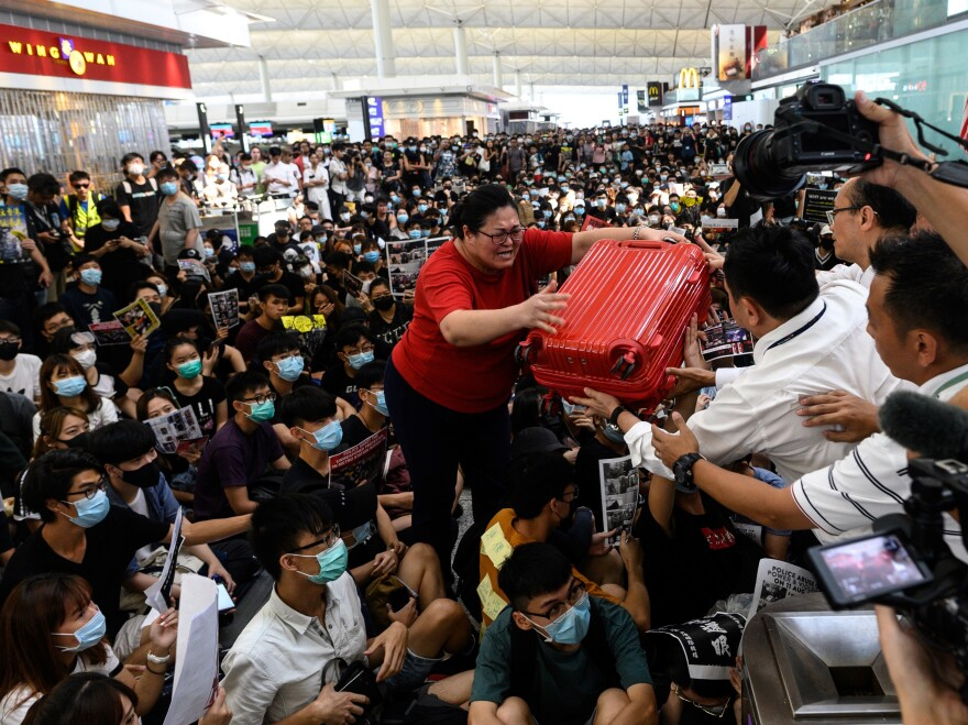 A tourist gives her luggage to security guards as she tries to enter the departures gate during another demonstration by pro-democracy protesters at Hong Kong International Airport on Tuesday.