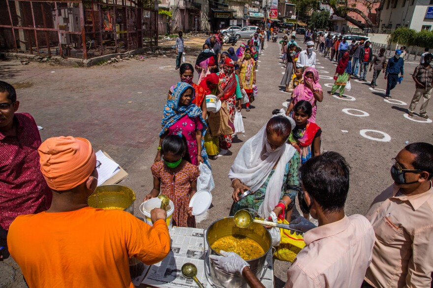 Disciples of the Hindu religious group known as Ramakrishna Mission distribute food to homeless migrant workers in New Delhi. They're standing in circles painted on the ground to maintain social distancing.