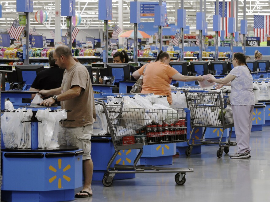 Despite slower growth, consumers like these, at a Wal-Mart in Arkansas, continued spending.