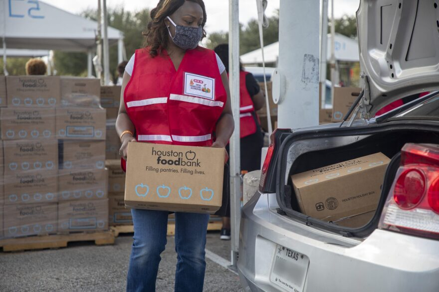 Cars line up at NRG to pick up boxes of food from the Houston Food Bank during the holiday season.