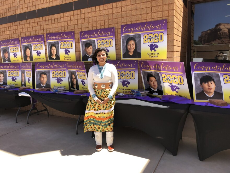 Photo of Tsosie standing next to posters of her classmates.