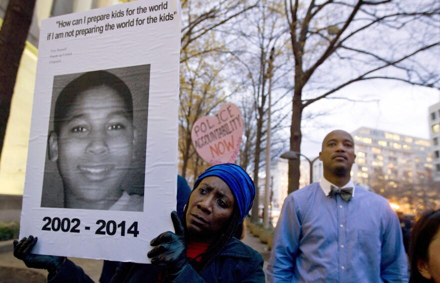 In a photo taken Dec. 1 of last year, Tomiko Shine holds up a picture of Tamir Rice during a protest. It has been nearly a year since then, but a grand jury has not reached a decision on the case.