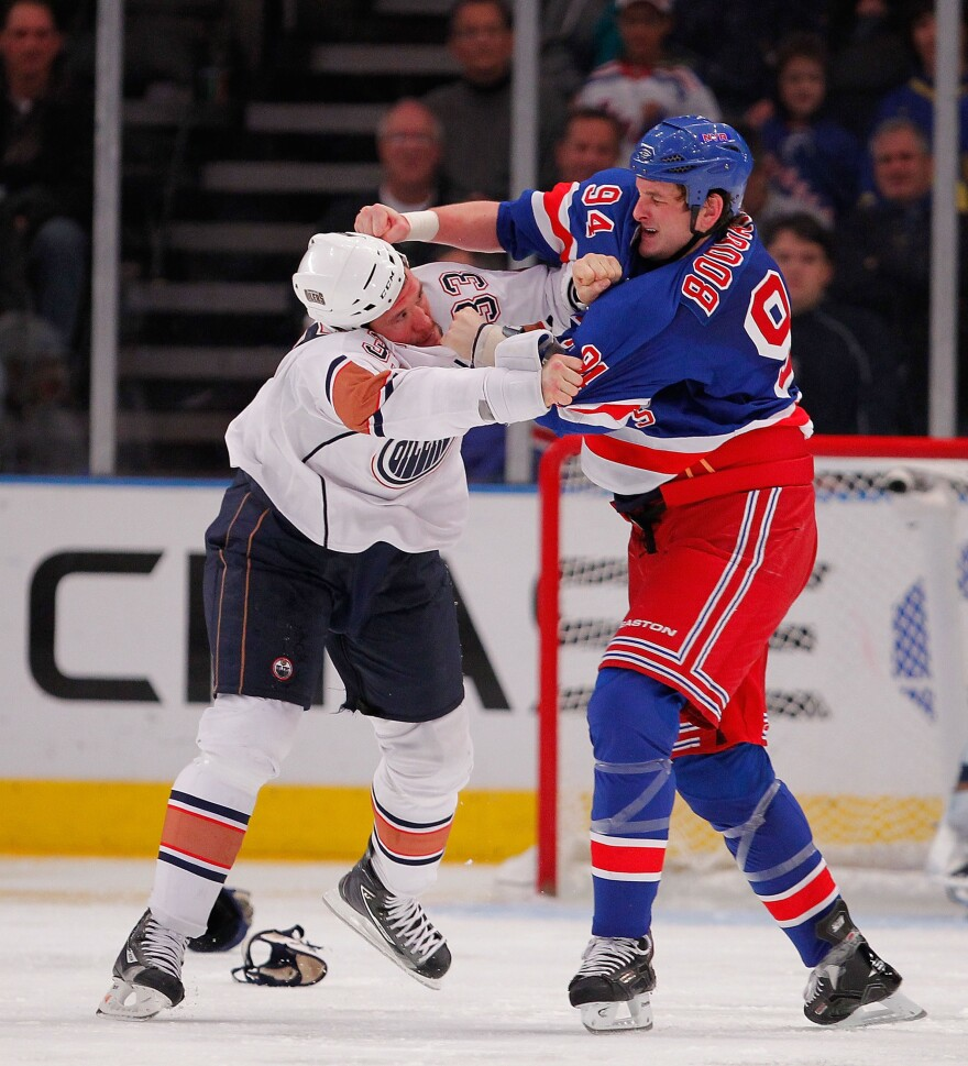 Steve MacIntyre of the Edmonton Oilers (left) fights with Derek Boogaard of the New York Rangers during a game in November 2010 in New York City.