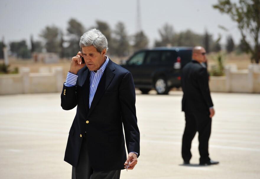 Secretary of State John Kerry speaks on the phone at Mafraq Air Base before boarding a helicopter to Amman on Thursday.