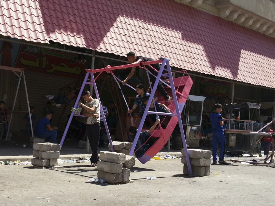 Iraqi children play on swings during an Eid al-Fitr celebration in the city of Mosul on Monday.