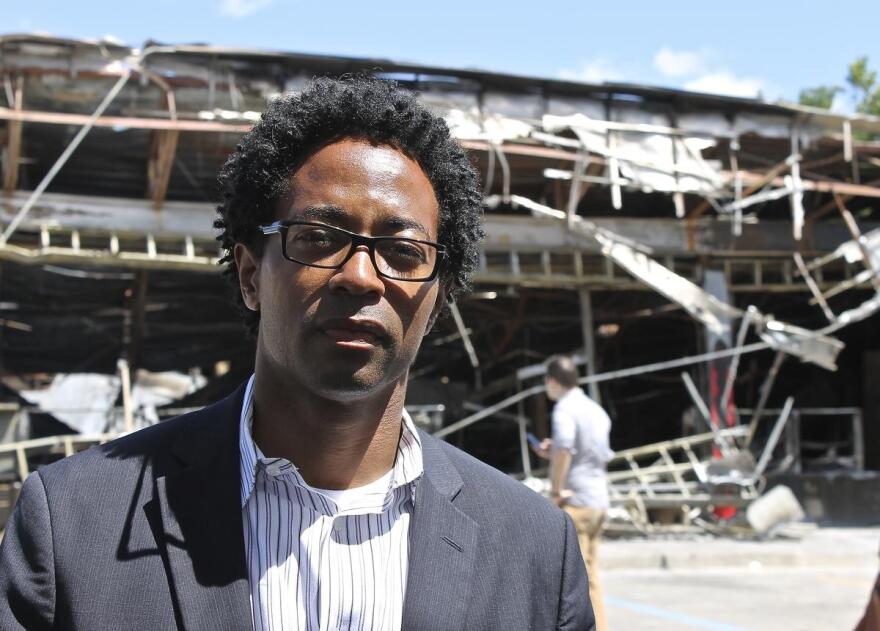 Wesley Bell stands near the burned down QuikTrip last year.