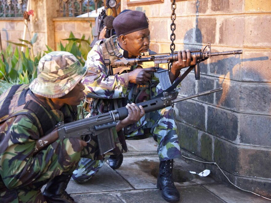 Kenya security personnel take cover outside Nairobi's upscale Westgate Mall after shooting started inside early Monday morning.