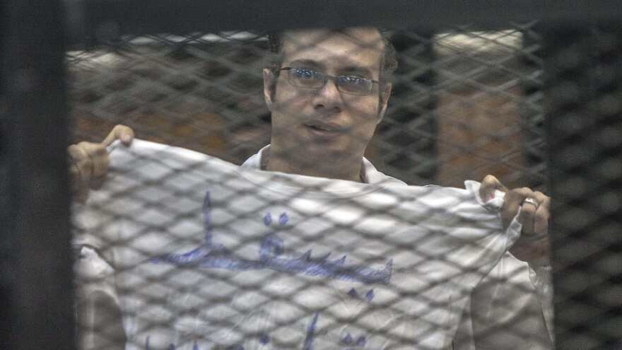 Egyptian political activist Ahmed Maher, shown during his trial last Dec. 8, shows a T-shirt calling for an end to the law that limits demonstrations. He is among a number of journalists and activists who have been writing letters from jail in Egypt.