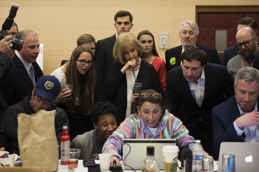 Lyda Krewson, surrounded by family, friends and campaign staffers, checks an update after 85 percent of precincts were tallied. (March 8, 2917)