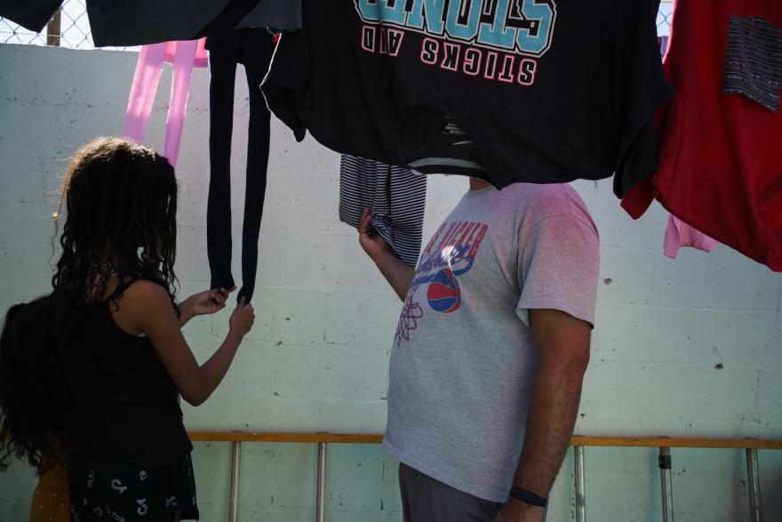 Carlo y sus hijas revisan la ropa que está secándose en el refugio para migrantes El Buen Samaritano, en Juárez.