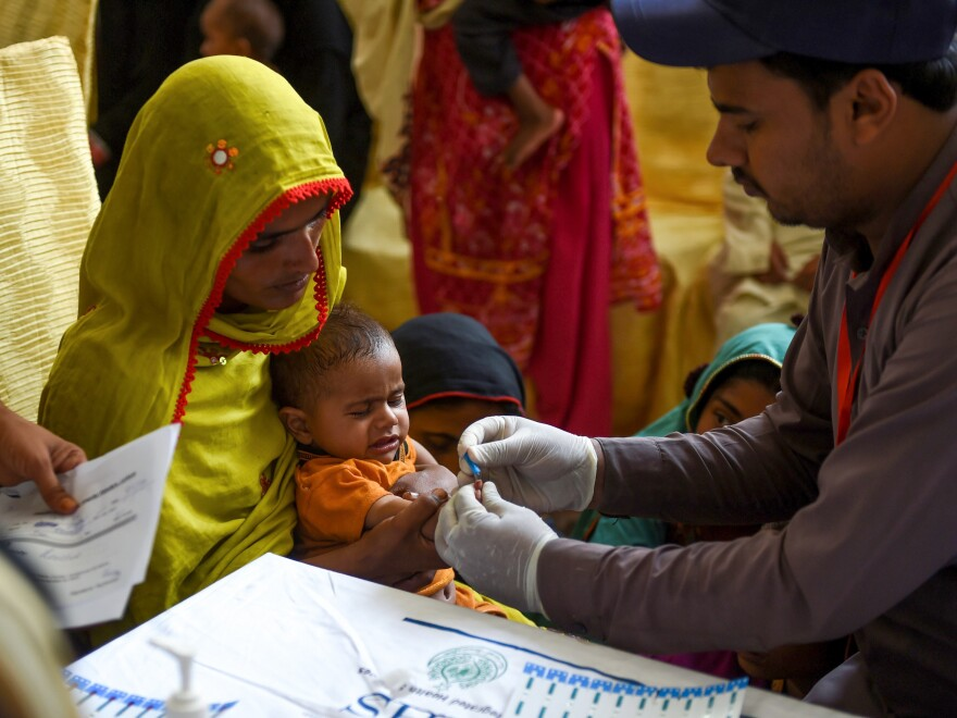 A paramedic takes a blood sample from a baby for a HIV test in Larkana, Pakistan, on May 9. The government is offering screenings in the wake of an HIV outbreak.