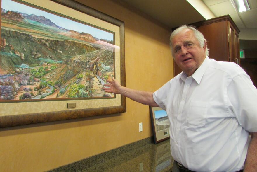 Ron Thompson points at a painting of St. George, Utah.