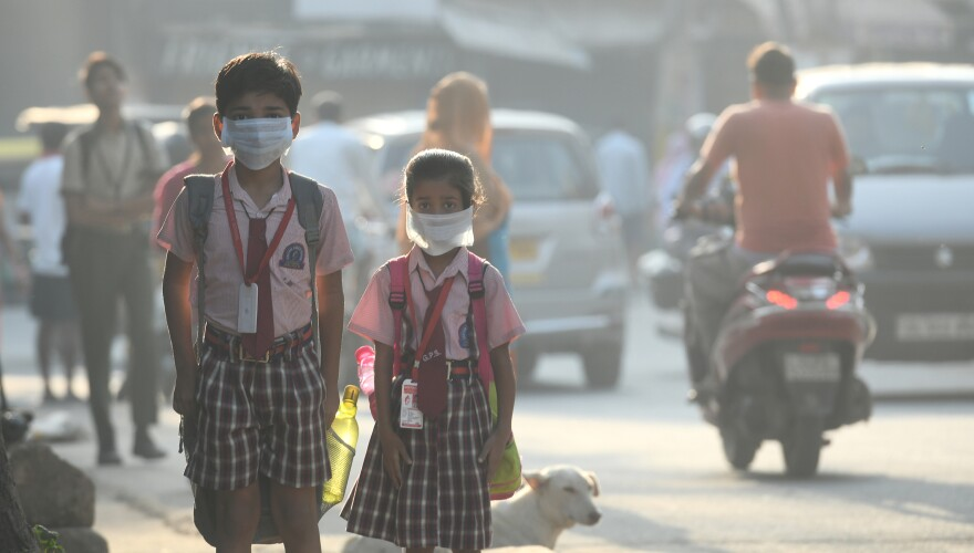 Students cover their faces with masks to protect themselves from air pollution in Delhi.
