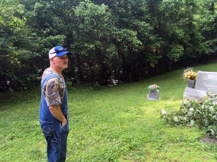 Todd Bentley stands in his family cemetery in Harless Creek in June, recalling the night of the 2010 flood. Bentley spent the night here with his teenage son when the creek swelled too high to cross safely.
