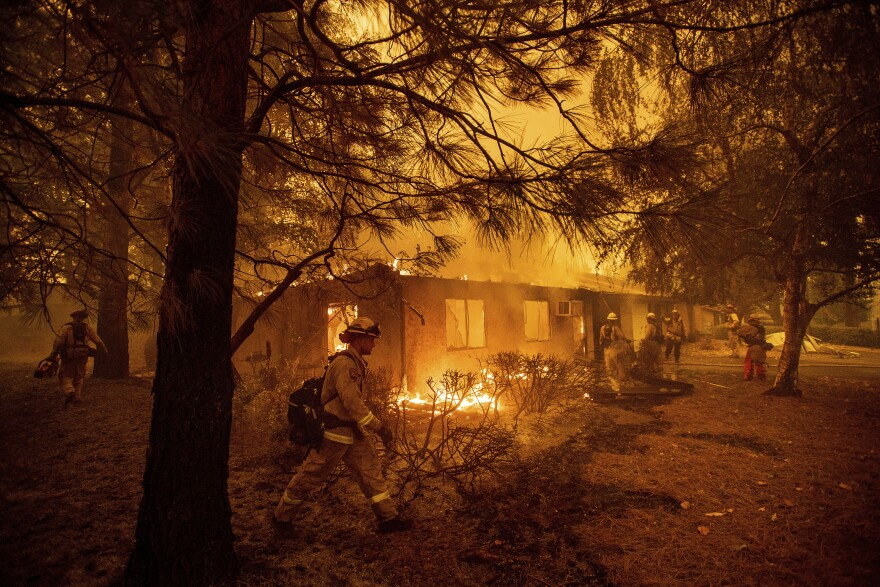 Firefighters work to keep flames from spreading through the Shadowbrook apartment complex as a wildfire burns through Paradise, Calif., on Friday, Nov. 9, 2018.