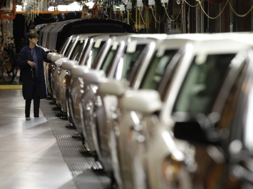 A line worker checks vehicles at the General  Motors Hamtramck assembly plant in November. GM is adding two shifts and about 2,500 jobs at the plant.