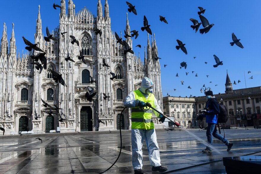 A man wearing protective gear sprays disinfectant on Piazza Duomo in Milan, in Lombardy, Italy, in March. Federico, who is from Lombardy, and his wife Liying, from Wuhan, pulled their younger child out of day care, and forbid both their children from going to playgrounds, weeks before anyone around them in Connecticut did the same.