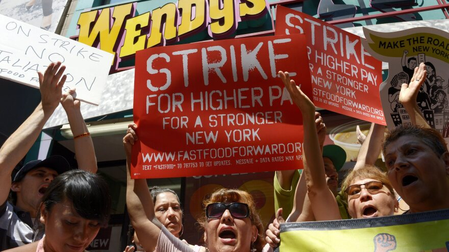 People gathered outside a Wendy's restaurant in New York City on Monday as part of a one-day strike calling for higher wages for fast-food workers.